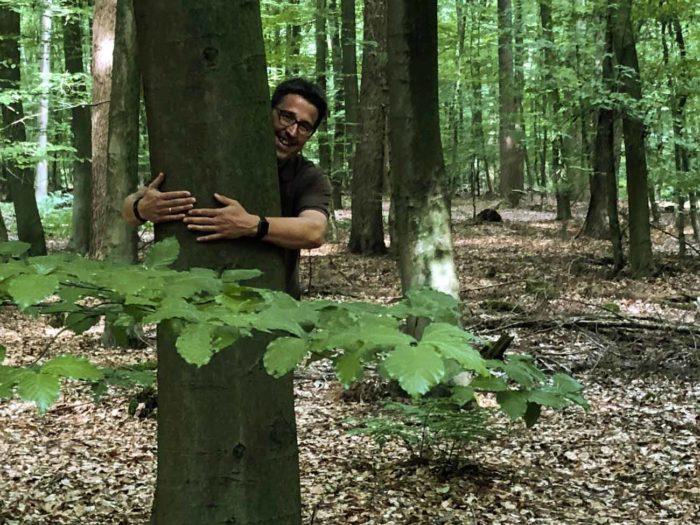 René Schneider umarmt einen Baum im Wald.