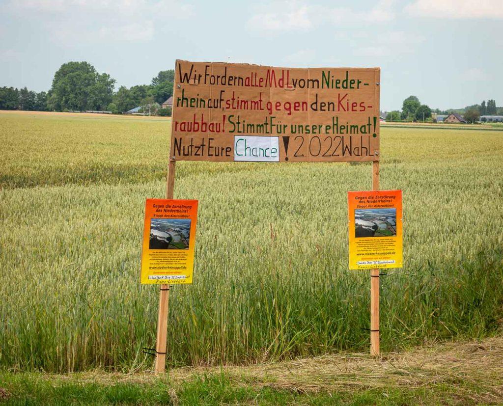 Schild am Wickrather Feld mahnt, politisch klug in Sachen Kiesabbau zu entscheiden.